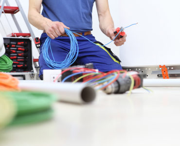 Electrician sorting wires on the floor