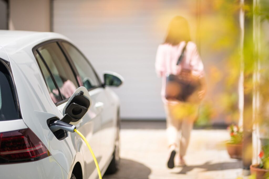 Women walking away from electric vehicle that has been put on charge