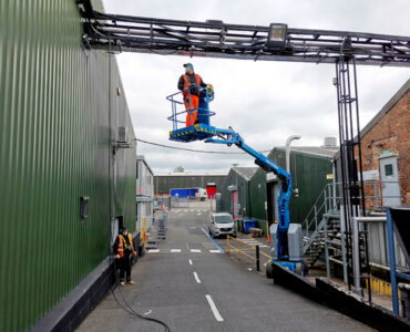 Electrician working in cherry picker attaching securing cables into trays