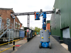 Electrician standing in a cherry picker dressing cables to tray